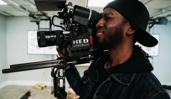 man-in-denim-jacket-holding-black-video-camera-3928528